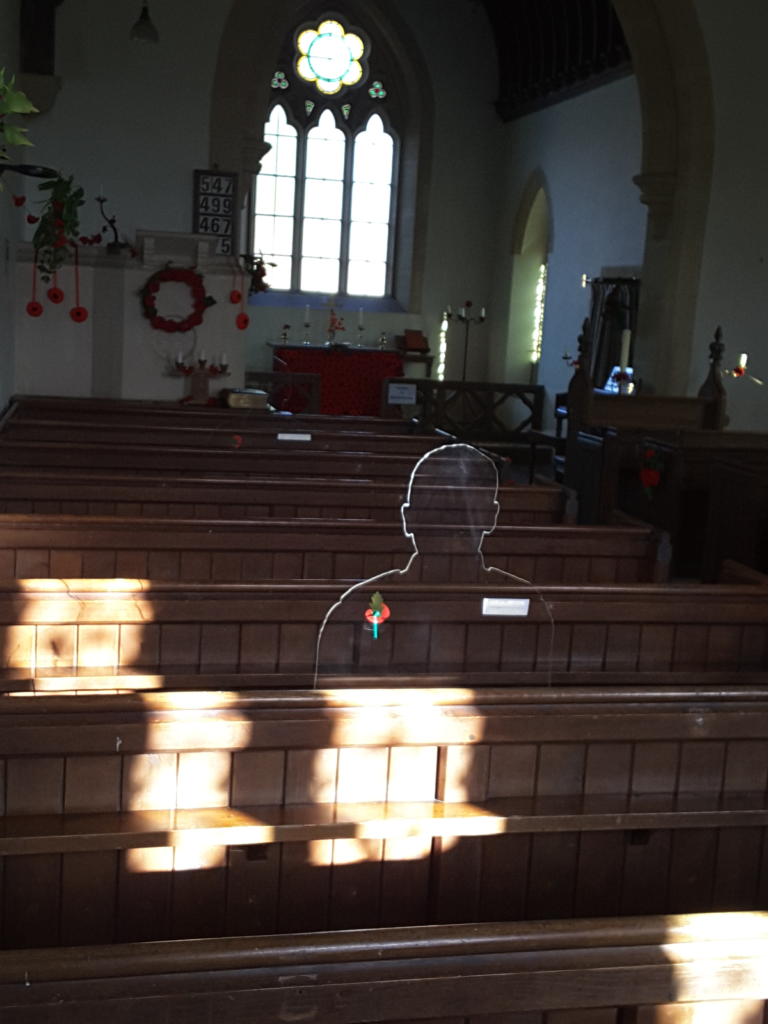 A silhouette in a church. The silhouette is in shadow i